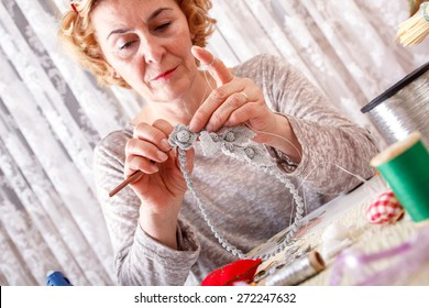 Creative senior woman making ornaments and jewelery by hand