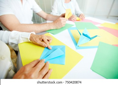 Creative seniors folding colorful paper at master-class of origami art