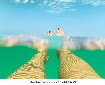 creative shot of 2 female legs relaxing under the water with pink polished nails on the water surface and blue sky in the background