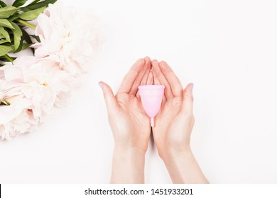 Creative shot of menstrual cup in woman hands. Feminine and lifestyle background.