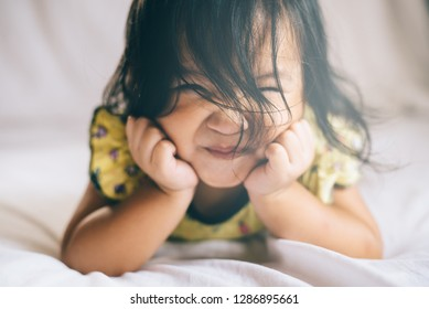 creative shot of smiling happy asian toddler on bed in her bedroom. concept of happiness, childhood, love and fun kids. ( shallow depth of field focus on hair )