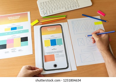 Creative sketch planning application process development prototype wireframe for web mobile phone. Graphic designer creating landing page for new website.