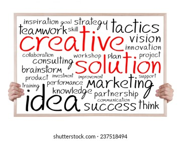 creative solution and other related words handwritten on whiteboard with hands