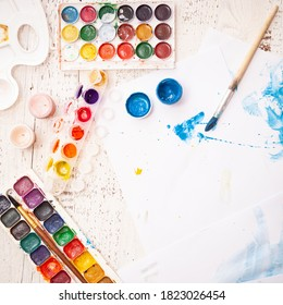 Creative space with brushes and paints. Creative ideas, creativity and early learning. Education concept. Top view of watercolors, paintbrush and some artistic stuff on white background