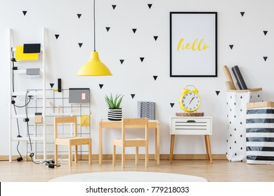 Creative space for a child with yellow lamp and wooden furniture
