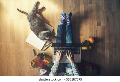 Creative space - Girl with her cat working from home.