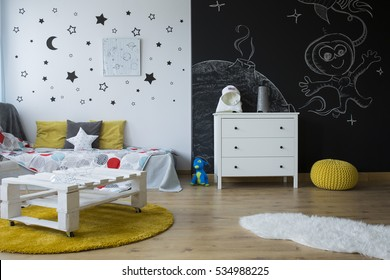 Creative space-themed children's room with blackboard wall