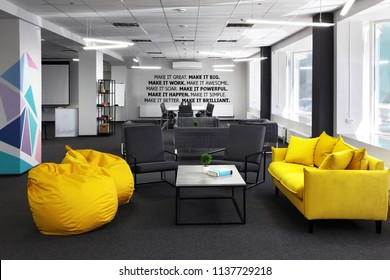 Creative space.With yellow sofa and yellow bean bag and coffe table in the first plan and Conference , meeting table and office armchair on the second plan. With motivation words on the wall