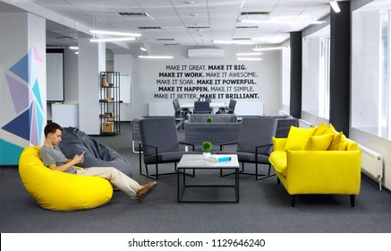 Creative space.With young man with smartphone sitting in yellow bean bag in the first plan and Conference , meeting table and office armchair on the second plan. With motivation words on the wall