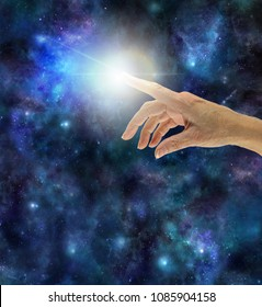 The Creative Spark of Universal Intelligence - female hand with index finger touching a bright white flash against a dark night sky Universe background with copy space beneath