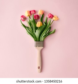 Creative spring concept made with paint brush and colorful tulip flowers on pastel pink background. Minimal nature flat lay.
