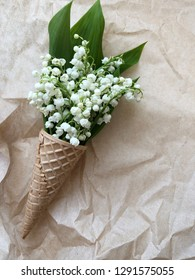 creative spring waffle cone with flowers on craft background