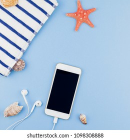 Creative square flat lay concept of summer travel vacations. Top view of beach towel, seashells, starfish and smartphone on pastel blue background with copy space in minimal style, template for text