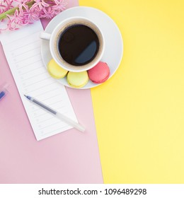 Creative square flat lay photo of coffee cup with macaroons and a notepad with copy space on pink and yellow background minimal style
