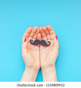 Creative square flatlay top view retro black paper photo booth props moustaches woman hands turquoise background copy space Men health awareness month fathers day masculinity concept blog social media