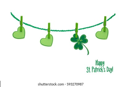 Creative St. Patricks Day concept photo of pinned  shamrocks and hearts made of paper on white background.