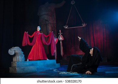 creative staging in the theater. Monk male and female beauty in a red dress.