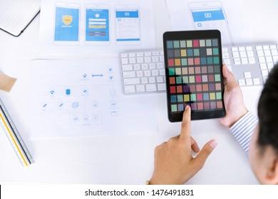 Creative startup UX UI designers team choosing color samples for designing mobile application screens layout.