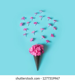 Creative still life. Bouquet of purple lilac flower in ice cream cone on pale pink background. Spring concept. View from above. Matte.