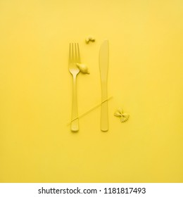 Creative still life photo of fork and spoon with raw pasta on yellow background.