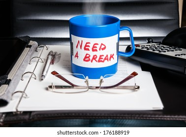 """Creative stress and vacation concept. A blue mug with a message """"Need a break"""" standing on a desk with business accessories."""