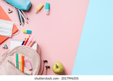 Creative student desk with colorful modern school supplies on blue and pink duotone background. Top view. Flat lay. Copy space. Back to school concept