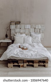 Creative studio apartment decor design with belongings of wooden pallets bed, plant in vase, books and cups. Books wall on background.