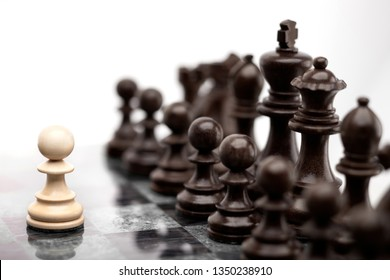 Creative success business concept meaningful photo of one pawn staying against full set of chess figures pieces on board.