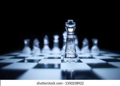 Creative success business concept meaningful photo of powerful chess king staying before the set of the same  colour figures pieces on checkerboard.