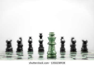 Creative success business concept meaningful photo of powerful chess king staying before the set of another colour figures pieces on checkerboard.