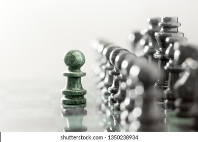 Creative success business concept meaningful photo of one pawn staying against full set of chess figures pieces on checkerboard.