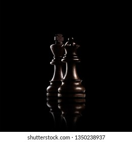 Creative success business concept meaningful photo of black wooden king and queen, the most powerful figures standing together against dark background.