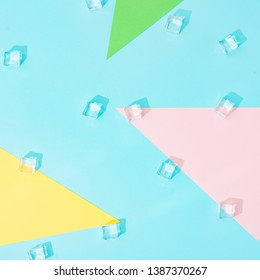Creative summer background composition with ice cubes and colorful paper shapes. Minimal top down.