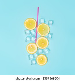 Creative summer background composition with lemon slices, straw and ice cubes. Minimal top down lemonade drink concept.