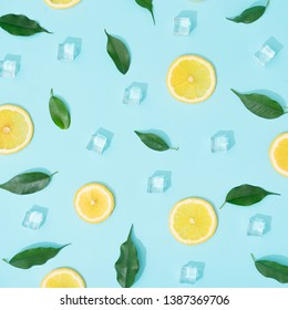 Creative summer background composition with lemon slices, leaves and ice cubes. Minimal top down lemonade drink concept.
