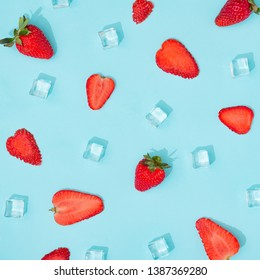 Creative summer background composition with strawberries and ice cubes. Minimal top down fruit concept.