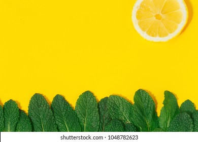 Creative summer background. Grass made of green mint leaves and sun of lemon on yellow background top view. Minimal summer concept. Flat lay