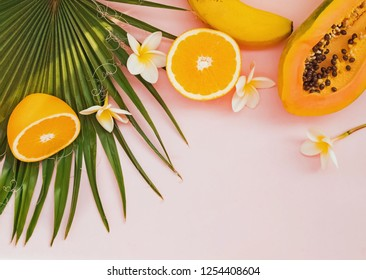 Creative summer composition with palm leaves, papaya, orange halves and plumeria flowers. Tropical background.