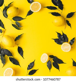 Creative summer pattern made of lemons and black leaves on yellow background. Fruit minimal concept. Flat lay.