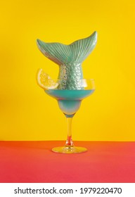 Creative summer vacation or party concept with blue coctktail and mermaid tail  on bold yellow and orange background. Fun tropical idea.