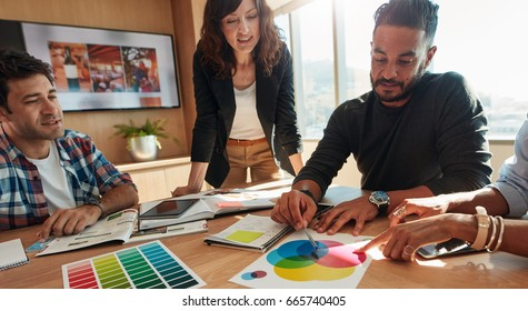 Creative team brainstorming in meeting room. Group of young adults sitting at the table with man showing color palette to colleagues.