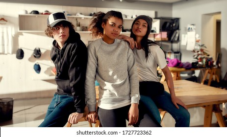 Creative team looking at camera while posing in custom apparel. Young man and women working at custom T-shirt, clothing printing company. Startup concept. Horizontal shot