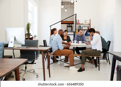 Creative team meet at a table in an office, one using phone