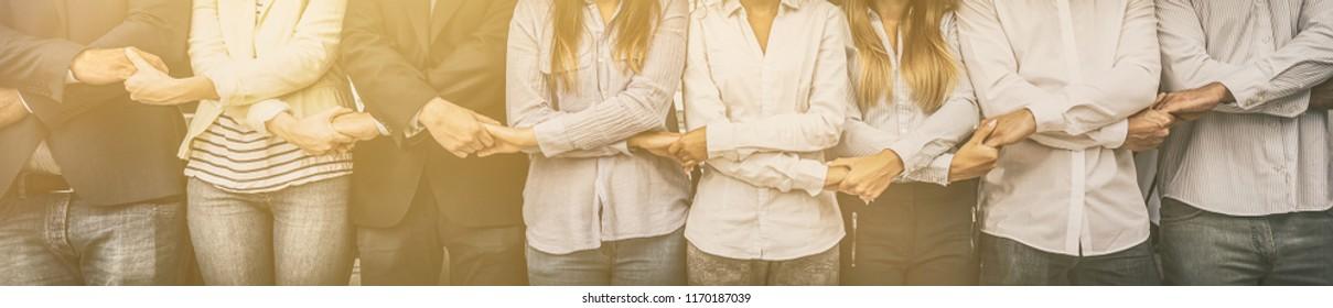 Creatief team dat handen samenkomt in de rij. Jonge zakenmensen houden elkaars hand vast. Eenheid en teamwork concept.