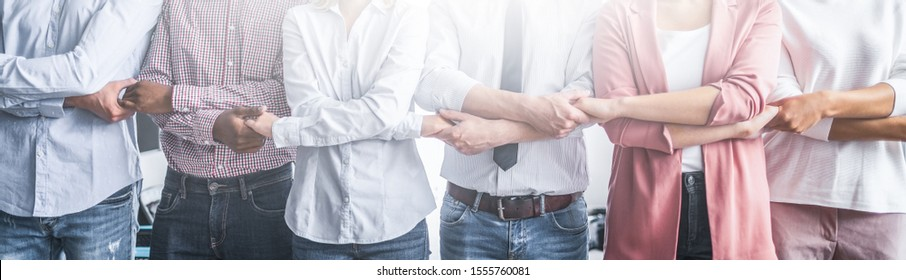 Creative team meeting hands together in line. Young business people are holding hands. Unity and teamwork concept.