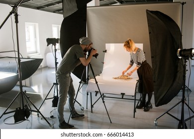 Creative team shooting commercials. Back view of photographer taking object shots with assistant in studio interior. photoshoot backstage