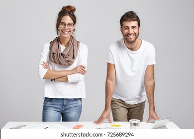 Creative team of two happy male and female colleagues in casual clothes standing at desk, looking at camera and smiling broadly after they presented their common project to boss and he approved it