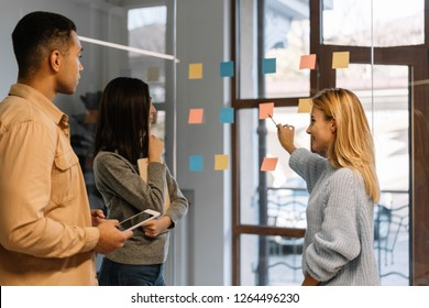 Creative team working together for startup project. Team building. Strategy planning. Brainstorming. Collaborate. Successful scrum master showing finger on sticky note, helping team reach consensus.