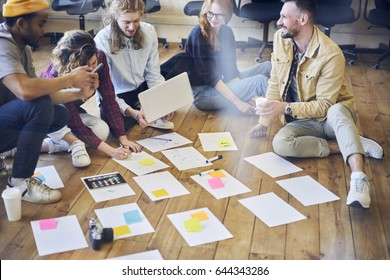Creative team of young male and female marketing experts collaborating during brainstorming session making solution while choosing successful concept for project organizing tasks and marking notes