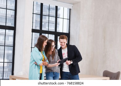 Creative teamwork. Positive office workers - two women and man stand near large wooden table and look at the tablet discussing something on the background of large windows in office
